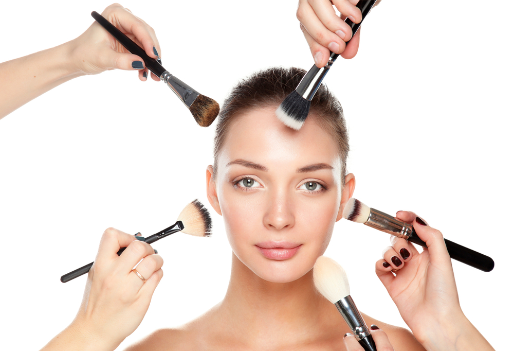 Woman getting make up down by multiple people
