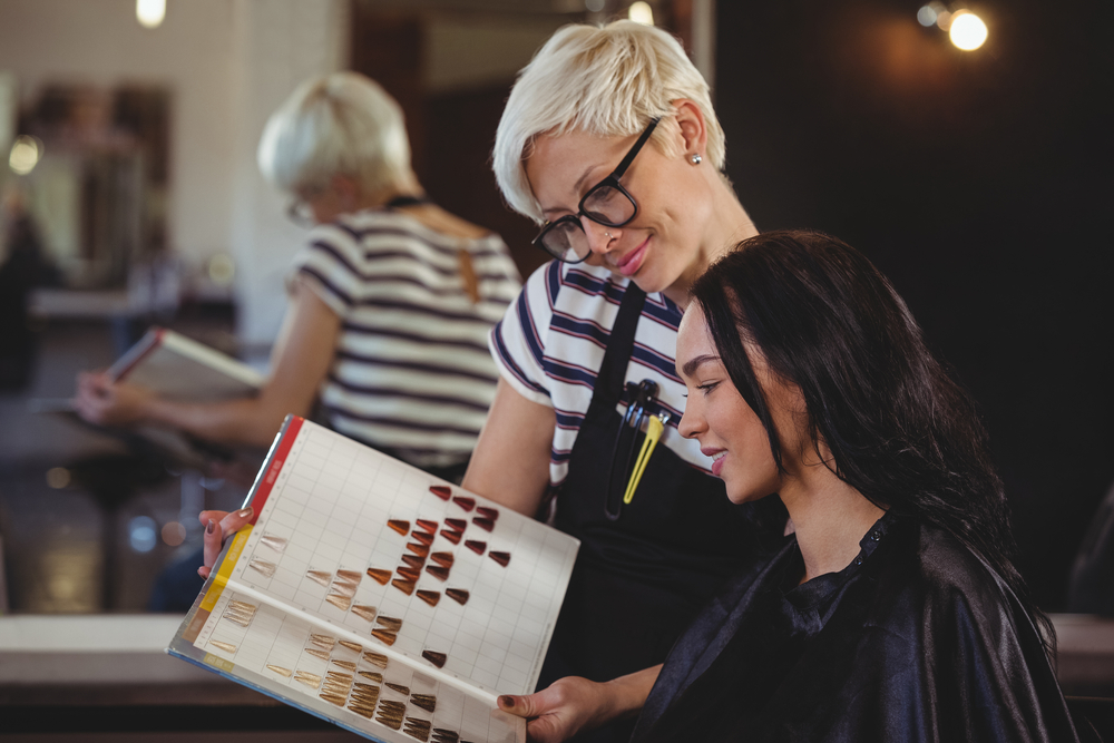 hair stylist showing hair colors to client