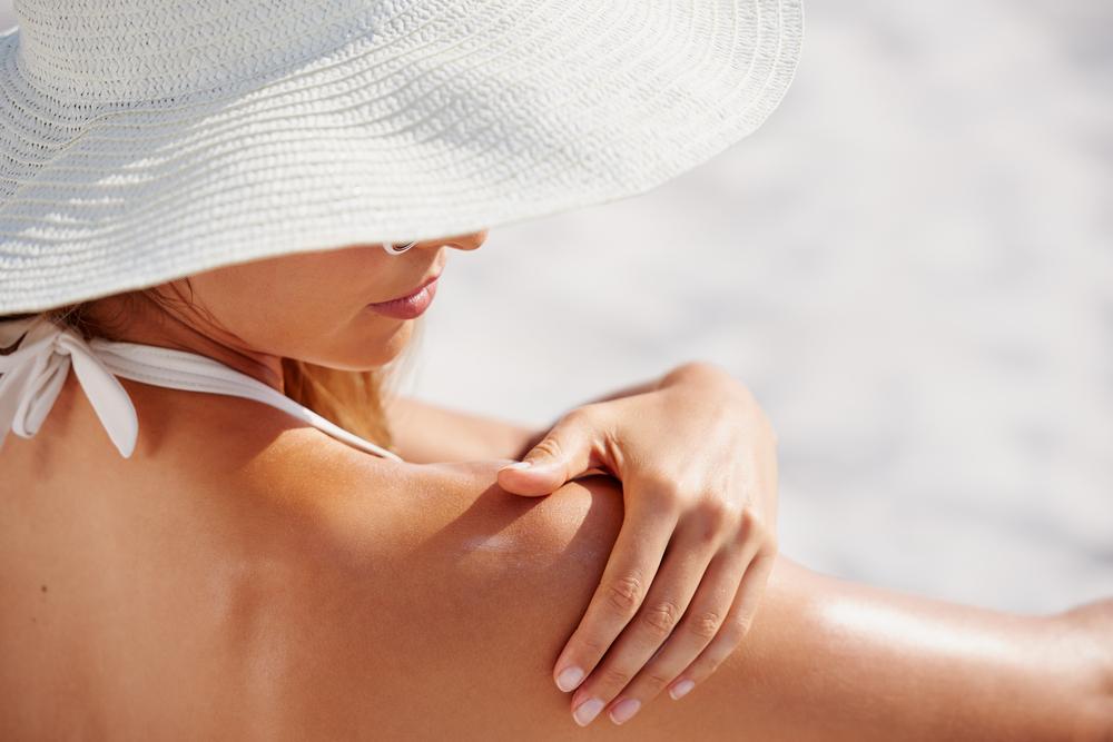 woman putting sunscreen on